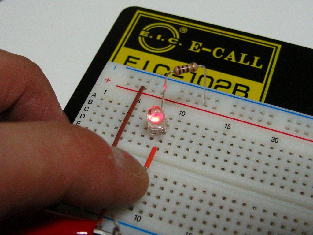 完成例です。プッシュスイッチを押すと回路が通じ、電気が流れます。その結果、発光ダイオード(LED)が点灯します。